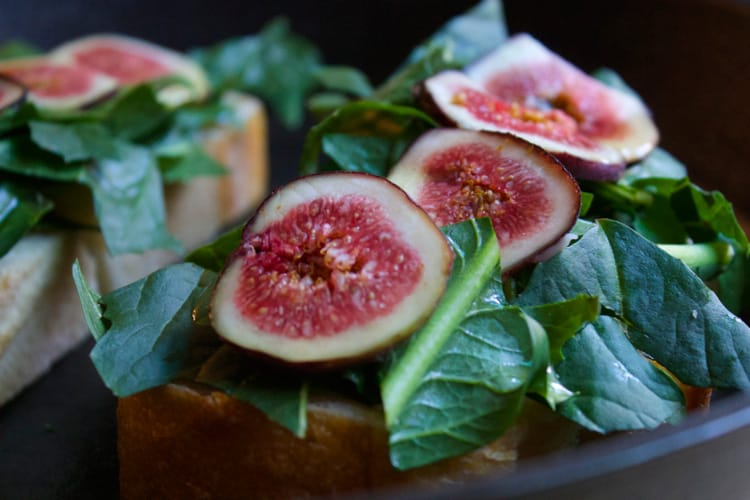 sliced figs and arugula on slices of bread