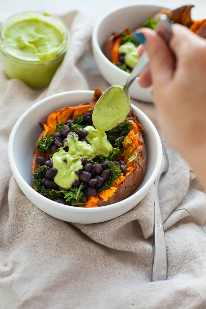 The best vegan loaded sweet potato topped with black beans, kale and a vegan green goddess dressing.