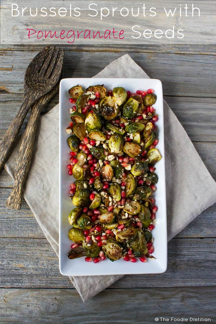 A beautiful holiday side dish, bright red pomegranate seeds make delicious crispy caramelized Brussels sprouts pop with festive flair. | @TheFoodieDietitian