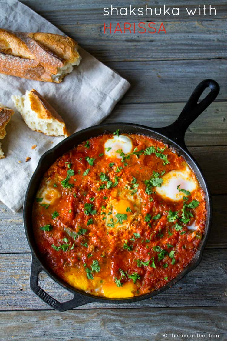 A traditional Middle Eastern dish with a North African twist, shakshuka with harissa (eggs baked in a spicy tomato stew) is a delicious savory dish to put on your Sunday brunch menu! | @TheFoodieDietitian