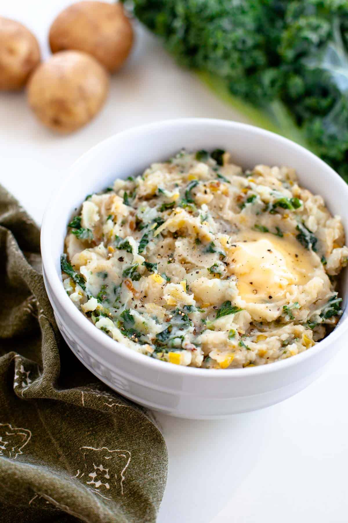 vegan colcannon in white bowl with three russet potatoes and kale in background