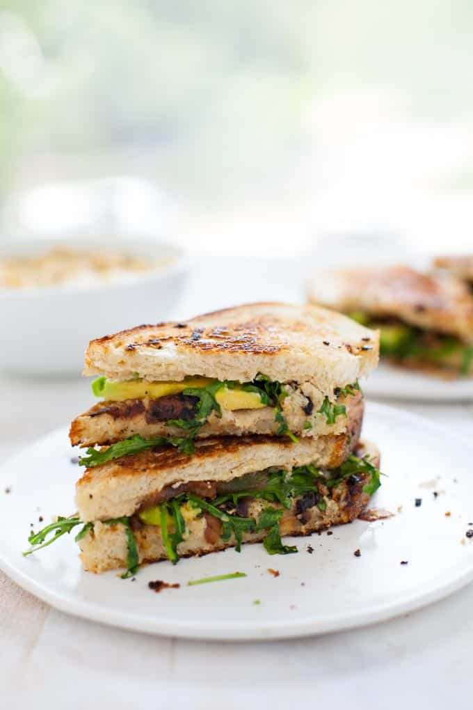 Cauliflower hummus is a new spread that's sure to rock any sandwich - this drool-worthy grilled cauliflower hummus sandwich is packed with avocado, caramelized onion and arugula. Lunch never looked better.