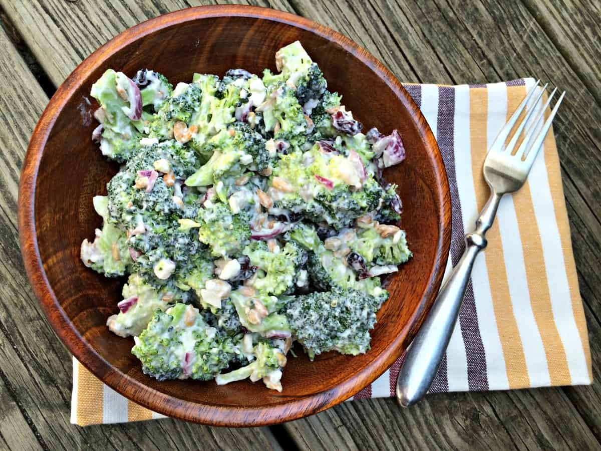 Creamy broccoli salad in a wooden bowl on a picnic table with a yellow striped napkin and fork