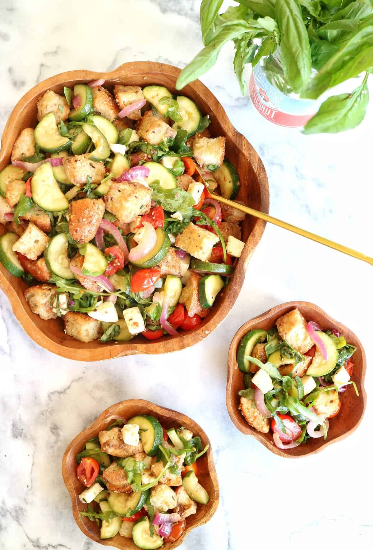 Large wooden bowl and two smaller bowls filled with roasted summer vegetable panzanella, on white marble table