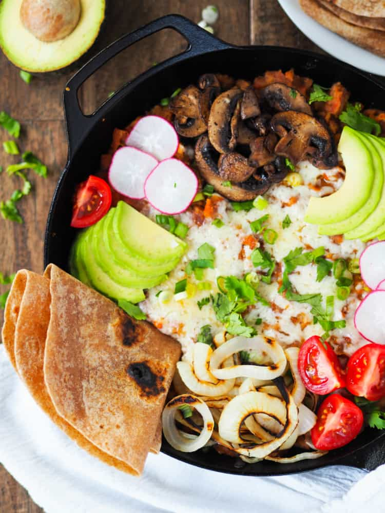 A deliciously cheesy and veggie fully loaded refried bean skillet! Weeknight dinners just got way more fun.