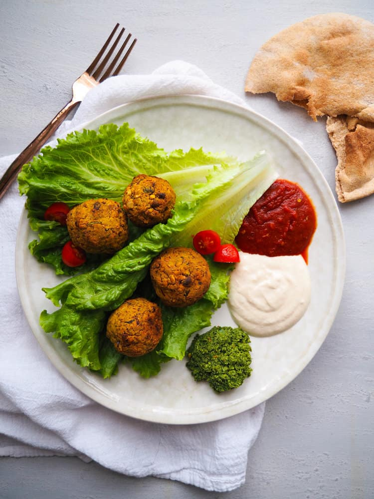 baked green falafel with three dips on a bed of lettuce, side of pita