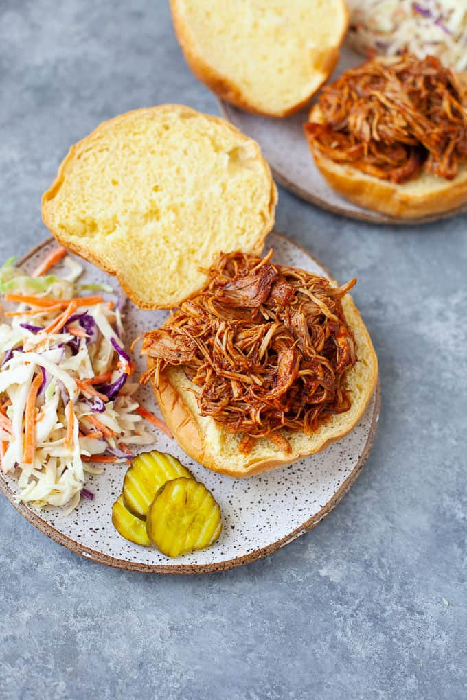Two plates of BBQ chicken sandwiches with a side of cole slaw and pickles