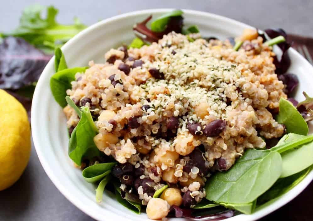 quinoa, chickpeas, and green leaves in a bowl
