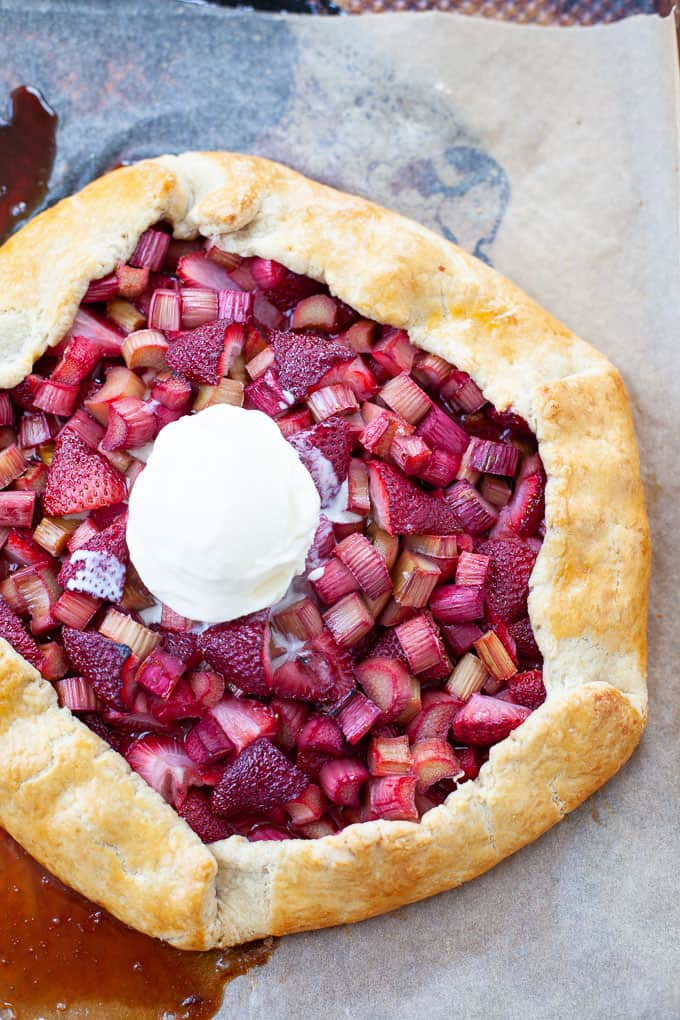 Fresh strawberry rhubarb galette with scoop of vanilla ice cream