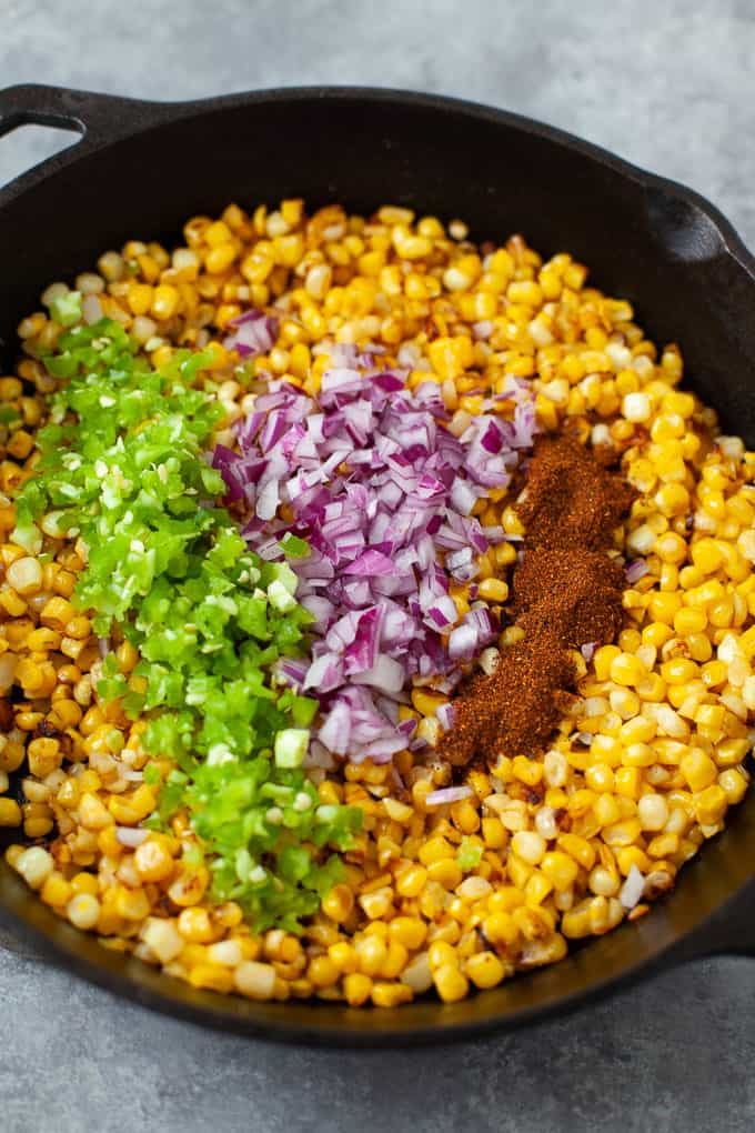 street corn, cilantro, onions, and chili powder in a skillet