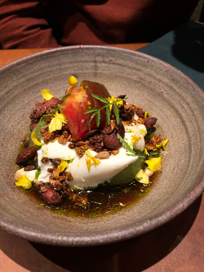 burrata with heirloom tomatoes, granola, and marigold