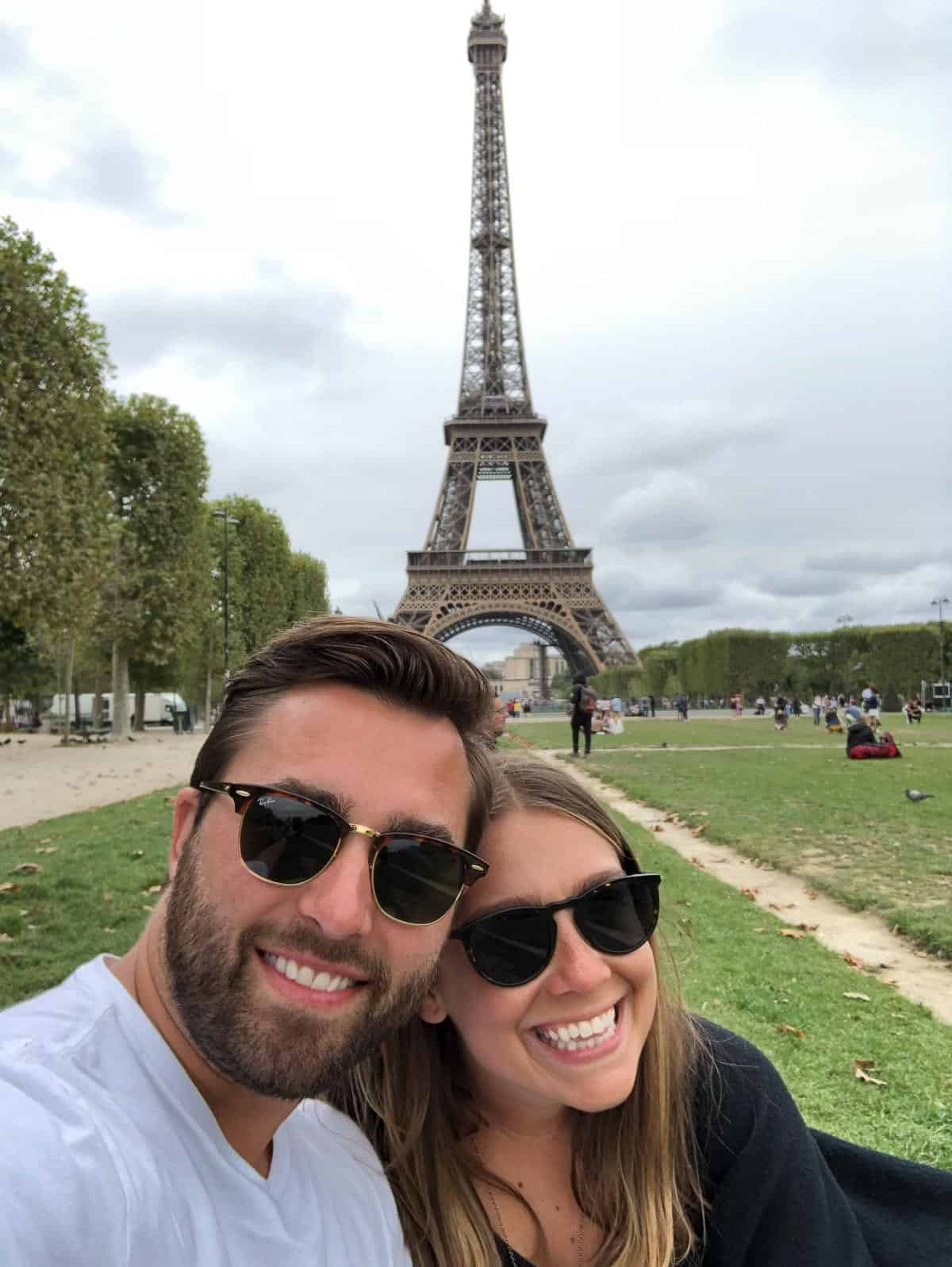Kara and Steve smiling in front of the Eiffel Tower