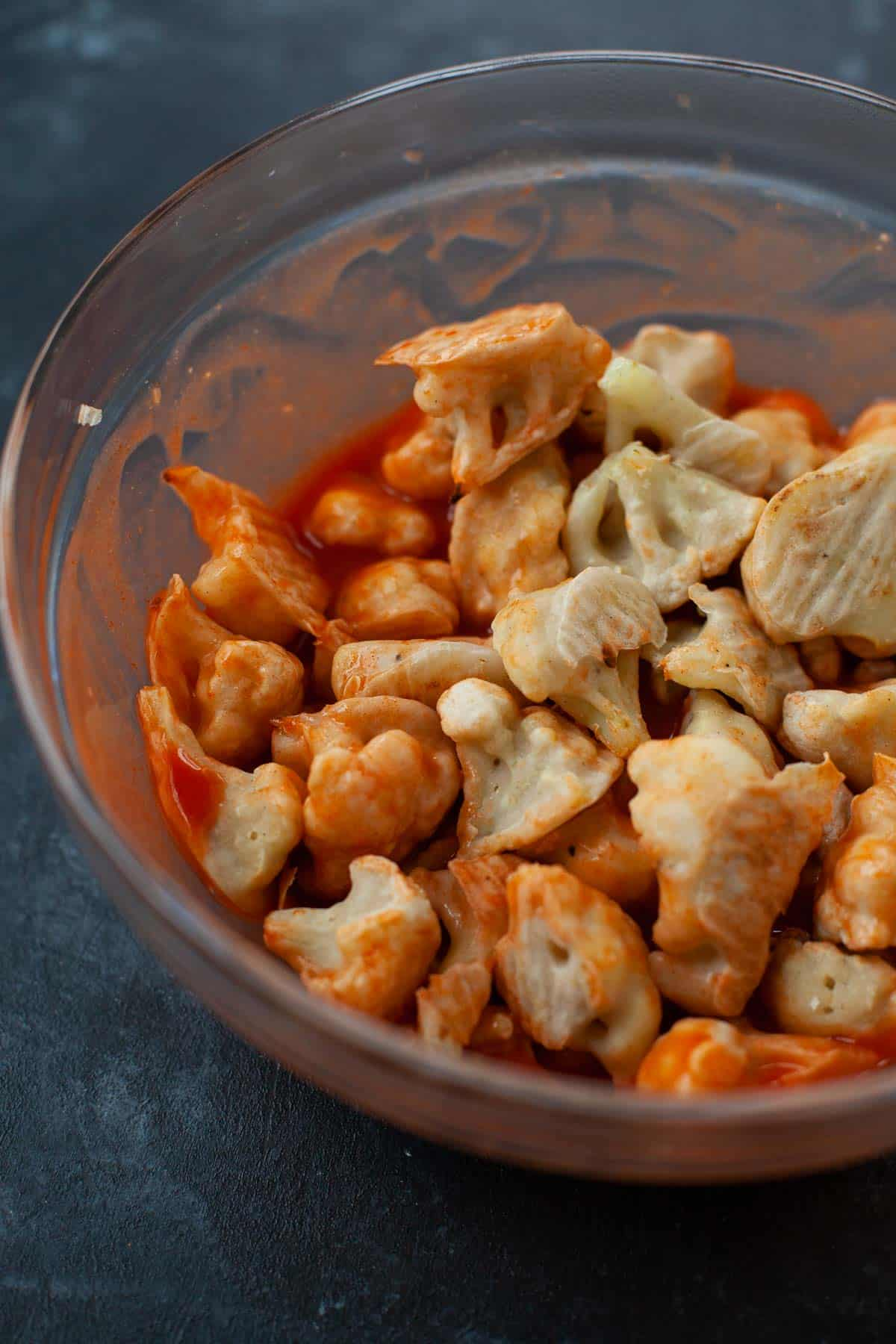 cauliflower pieces in bowl with hot sauce