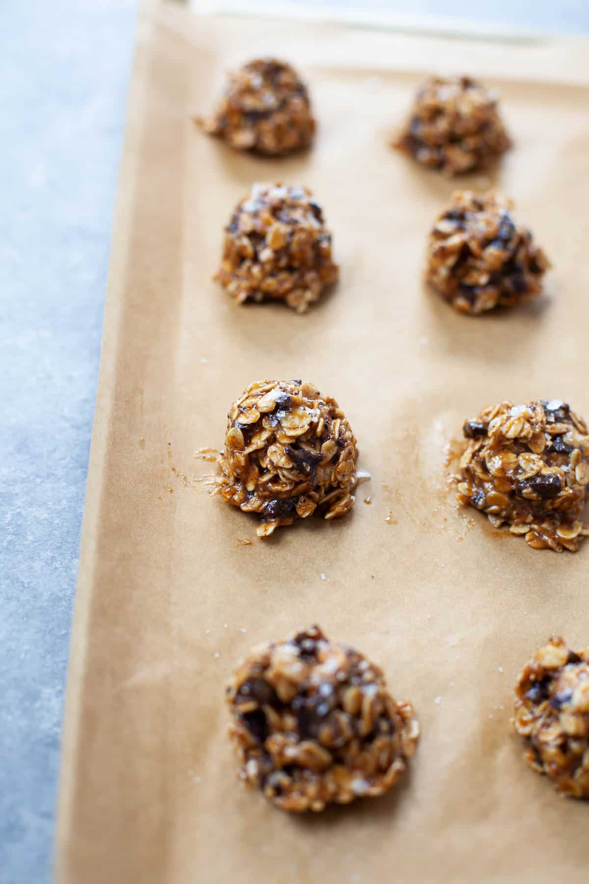 close up shot of cookie dough rolled into balls on a parchment lined baking sheet