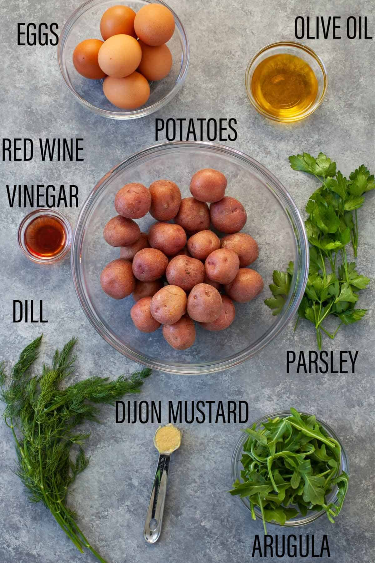 eggs, olive oil, red wine vinegar, potatoes, dill, dijon mustard, parsley, and arugula spread out on a counter