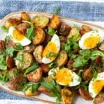 roasted potato salad with egg, arugula, and scallions