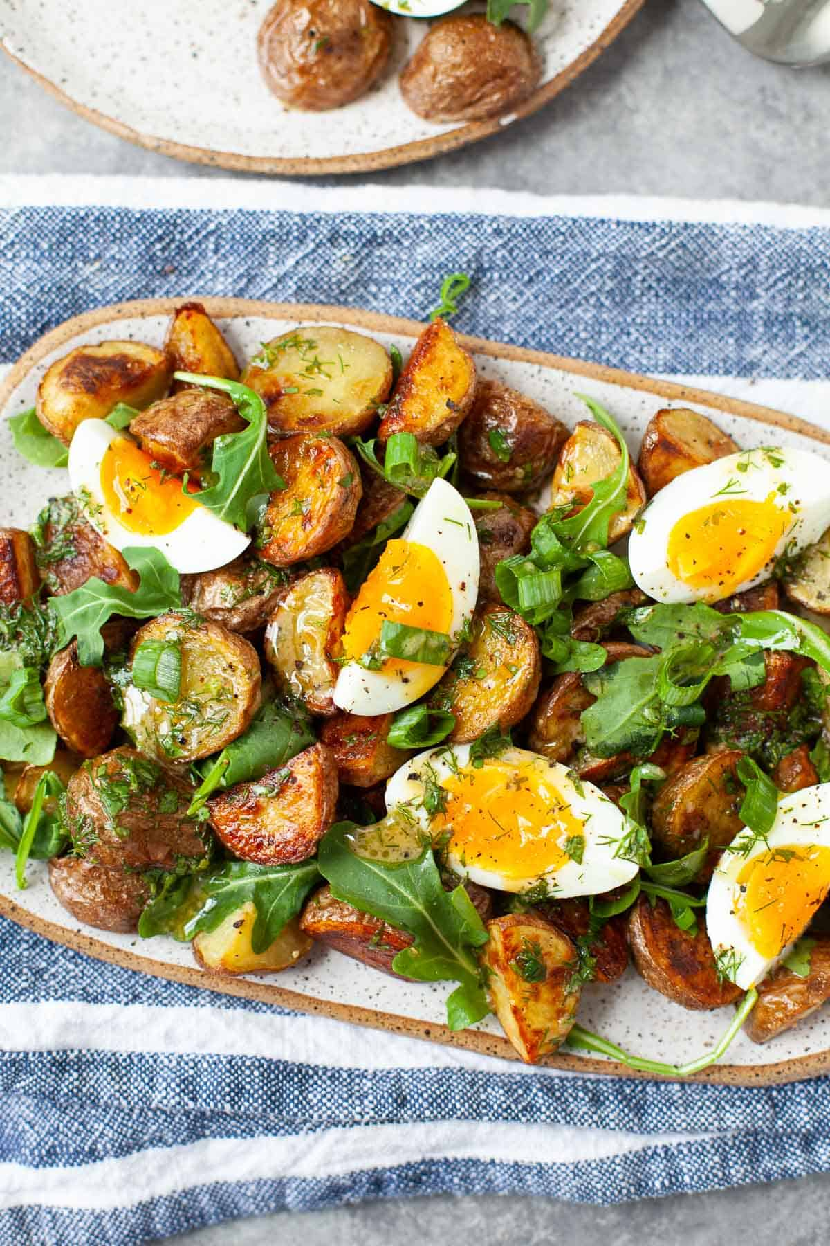 roasted potato salad with soft boiled eggs, arugula, and scallions