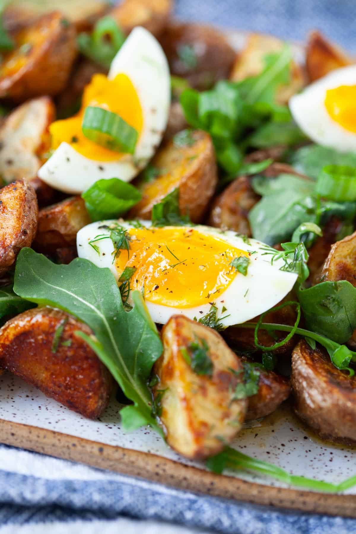 soft boiled eggs, arugula, and scallions mixed with roasted potatoes