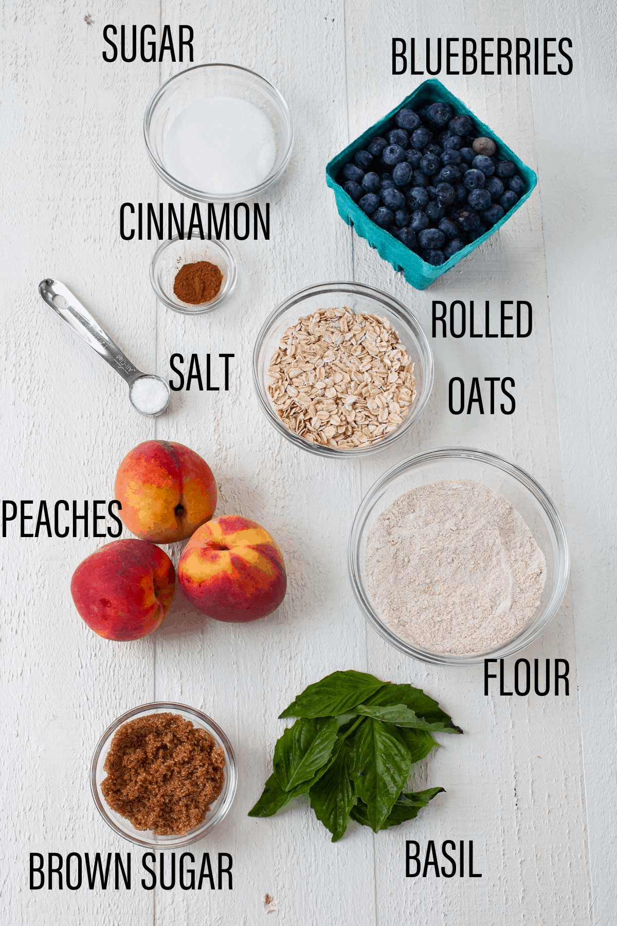 blueberries, peaches, basil laid out on counter with sugar, cinnamon, flour and brown sugar in bowls