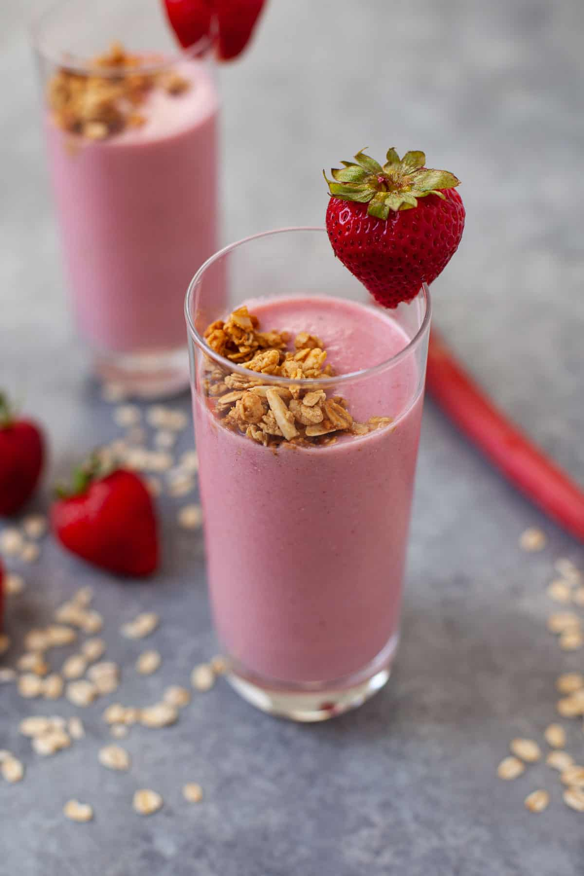 two glasses of strawberry rhubarb pie smoothie with fresh strawberries and granola for garnish