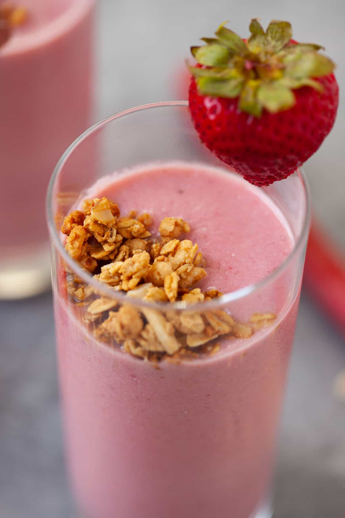 glass filled with strawberry rhubarb smoothie with nutty granola and fresh strawberry for garnish