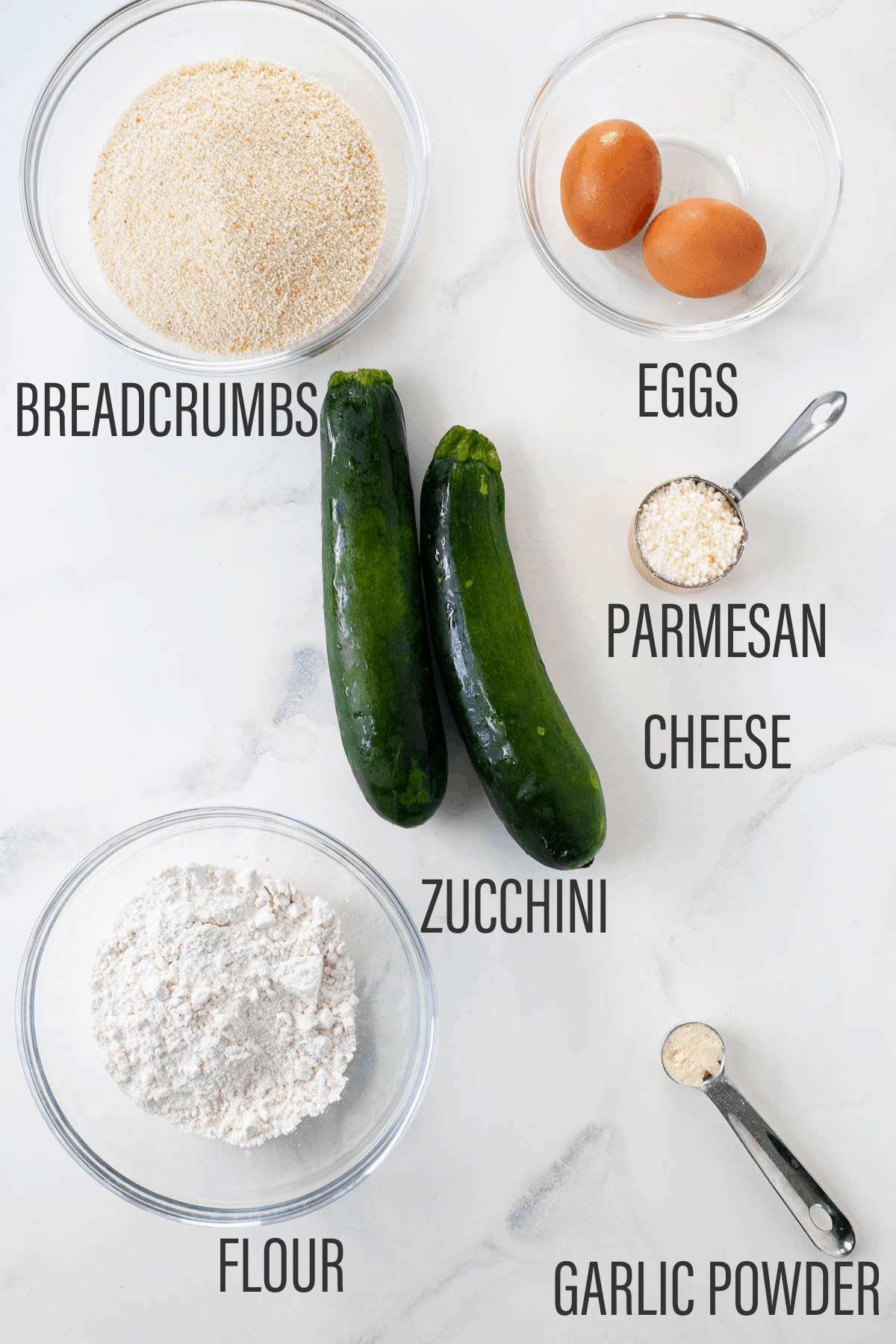 breadcrumbs, eggs, zucchini, parmesan cheese, flour, and garlic powder laid out on counter