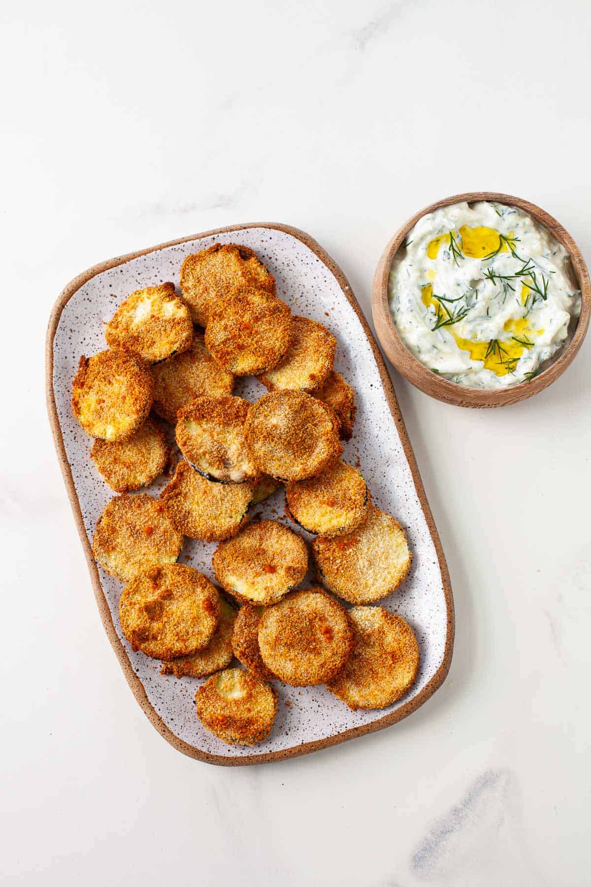 crispy zucchini chips on a plate next to a bowl of dipping sauce