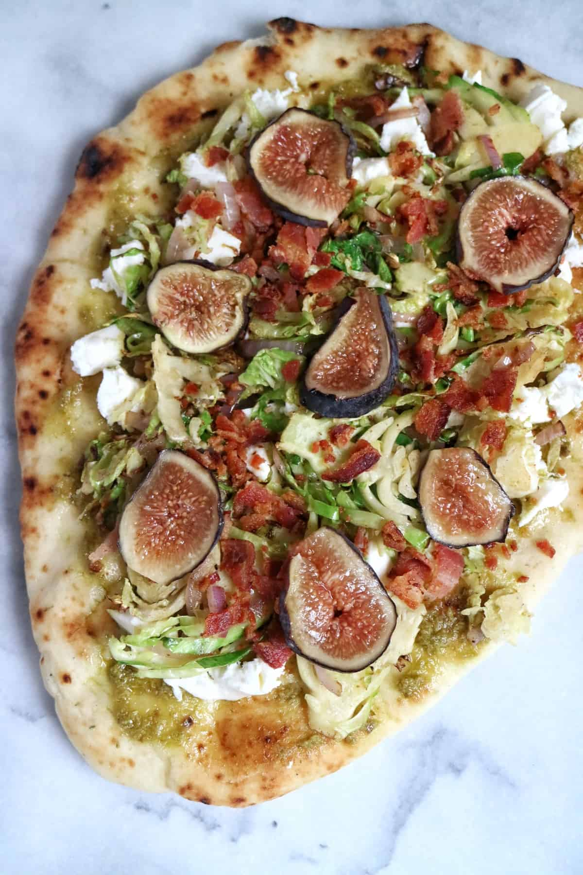fresh figs on top of flatbread pizza with brussels and bacon