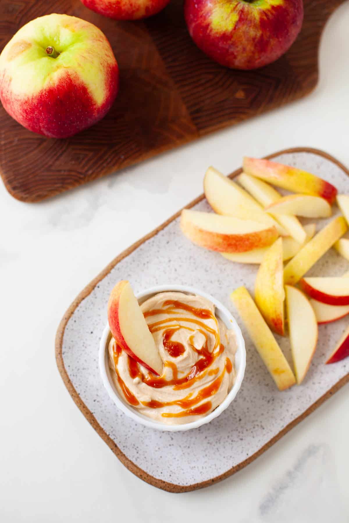 peanut butter apple dip on a place with sliced apples with apples on cutting board