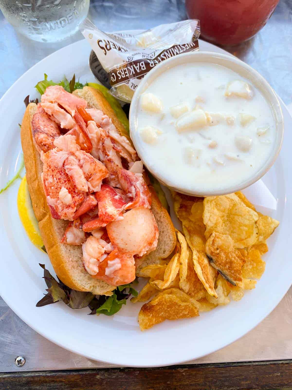 lobster roll served with clam chowder and chips
