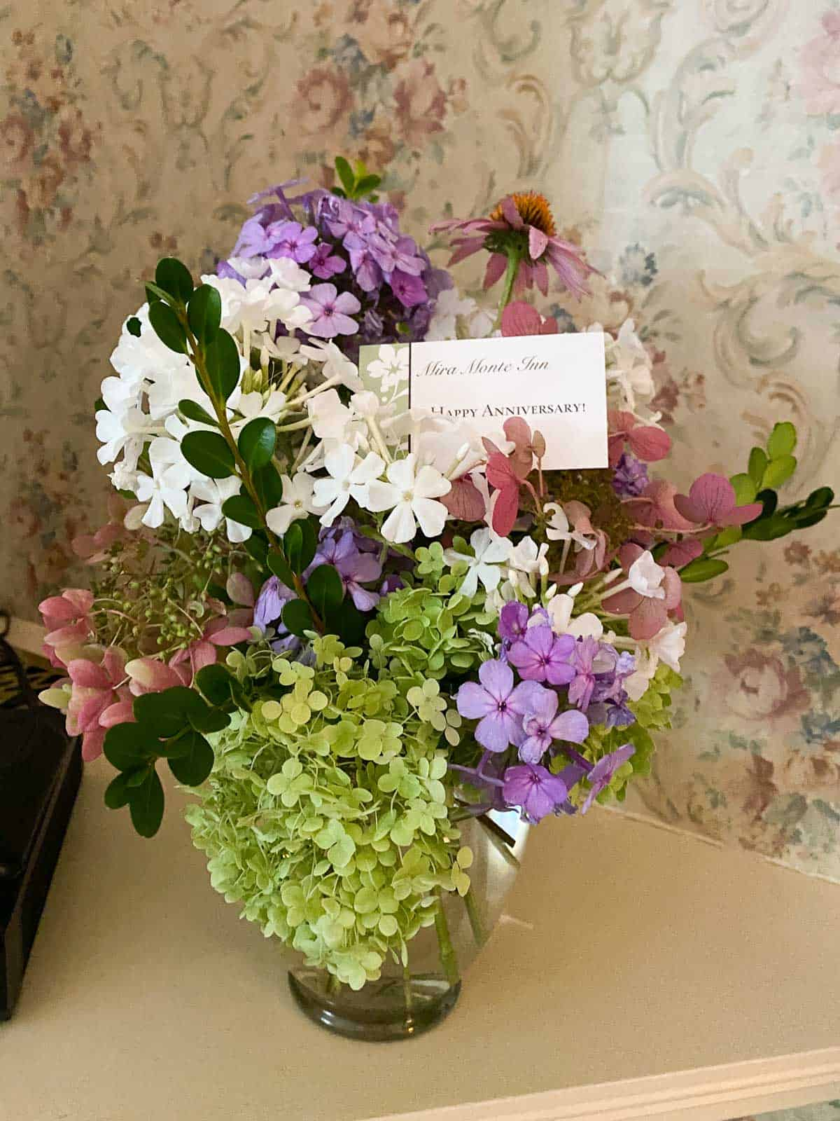 fresh flowers in a glass vase with a Happy Anniversary card