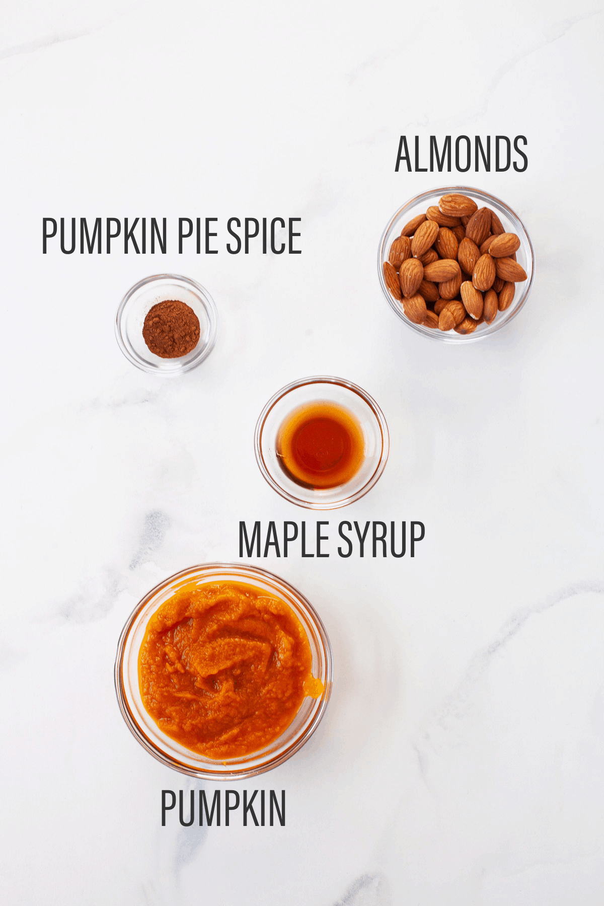 pumpkin pie spice, almond, maple syrup, and pumpkin separated in glass bowls