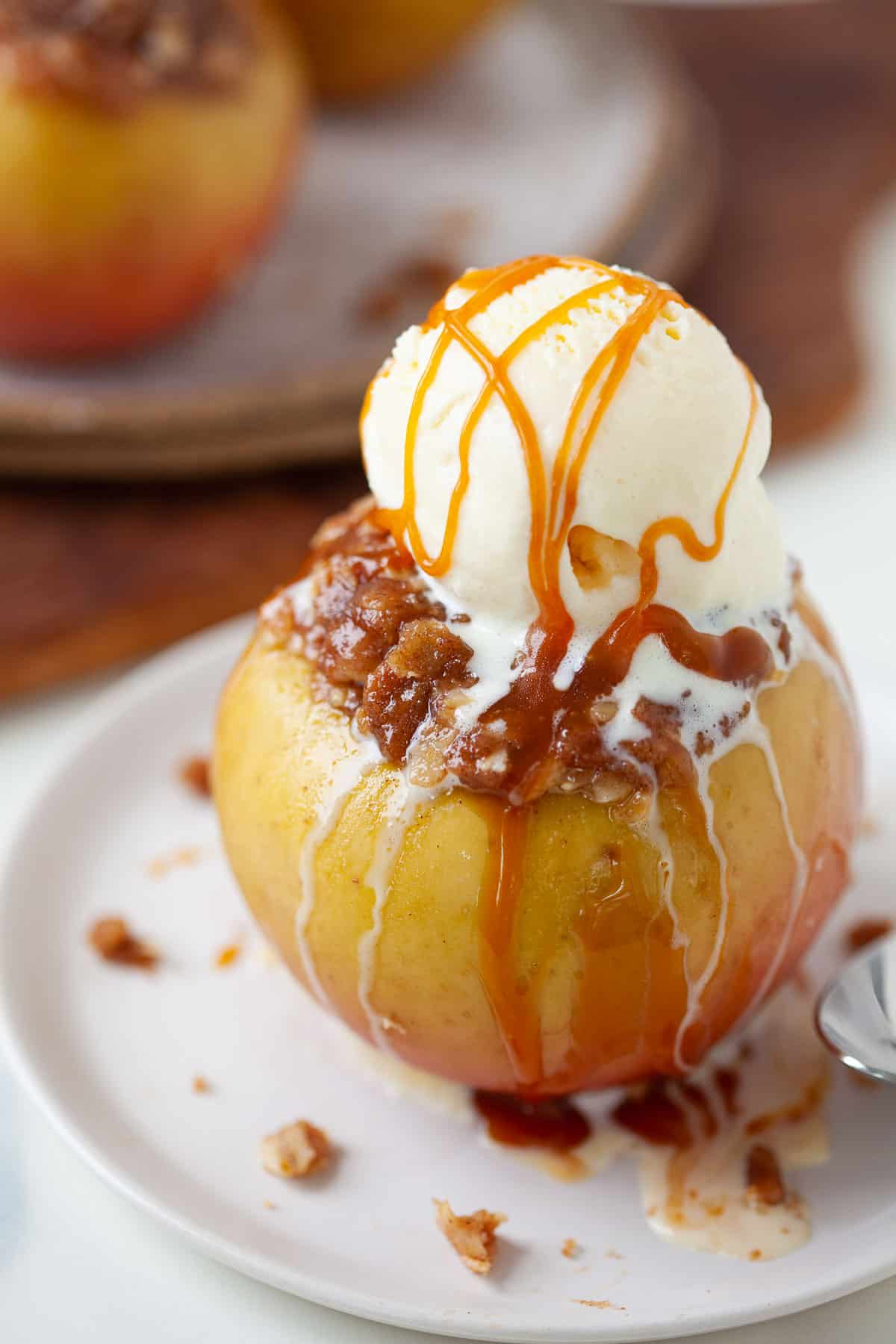 baked apple with oat and cinnamon mixture with scoop of vanilla ice cream and caramel drizzle