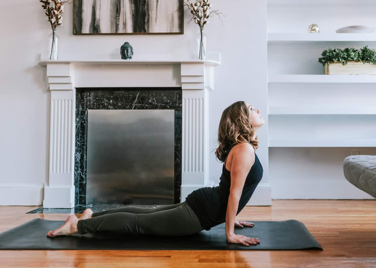 Kara is on a yoga mat demonstrating a yoga pose in front of a fireplace in her living room