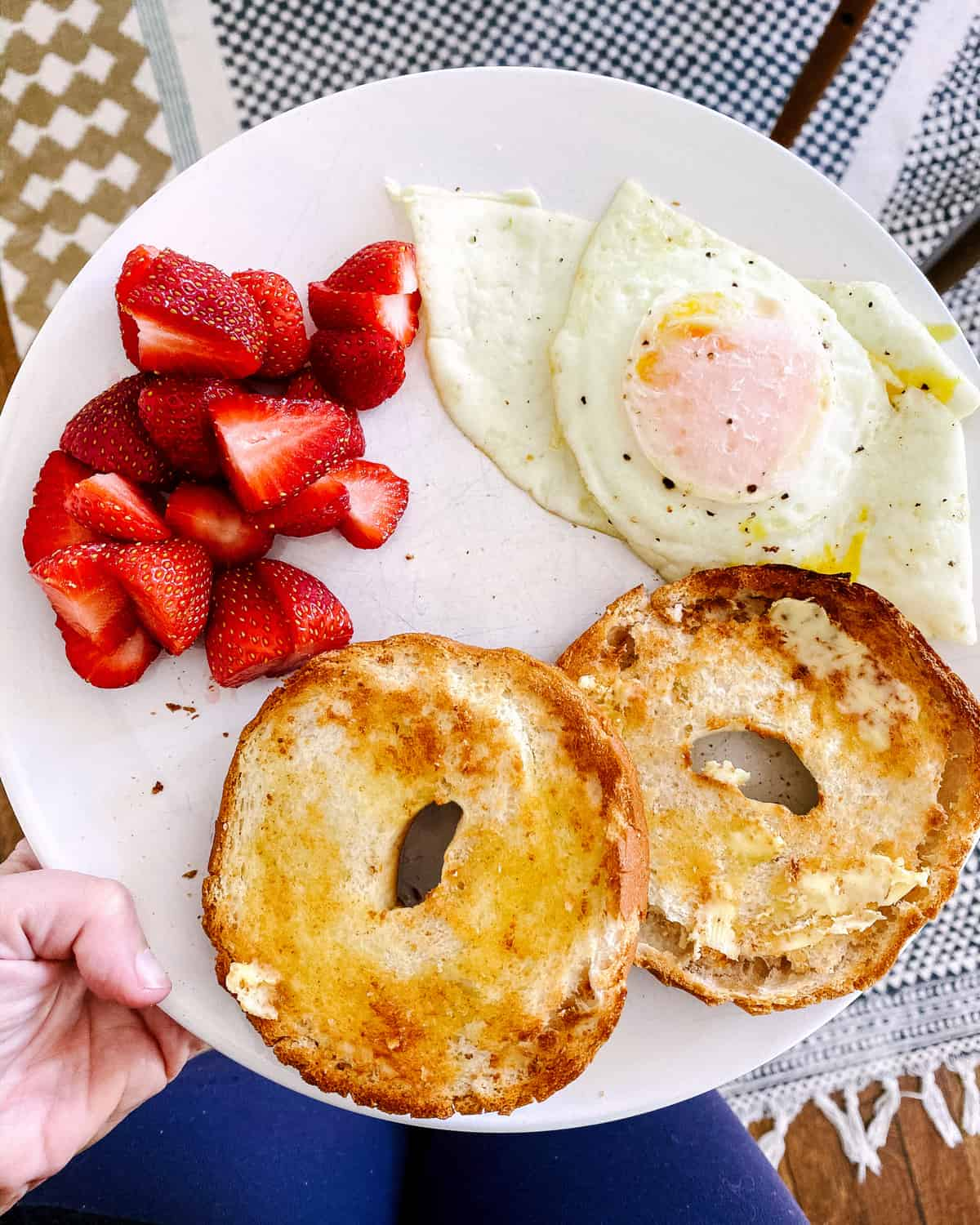 plate filled with toasted bagel, poached egg, and sliced strawberries