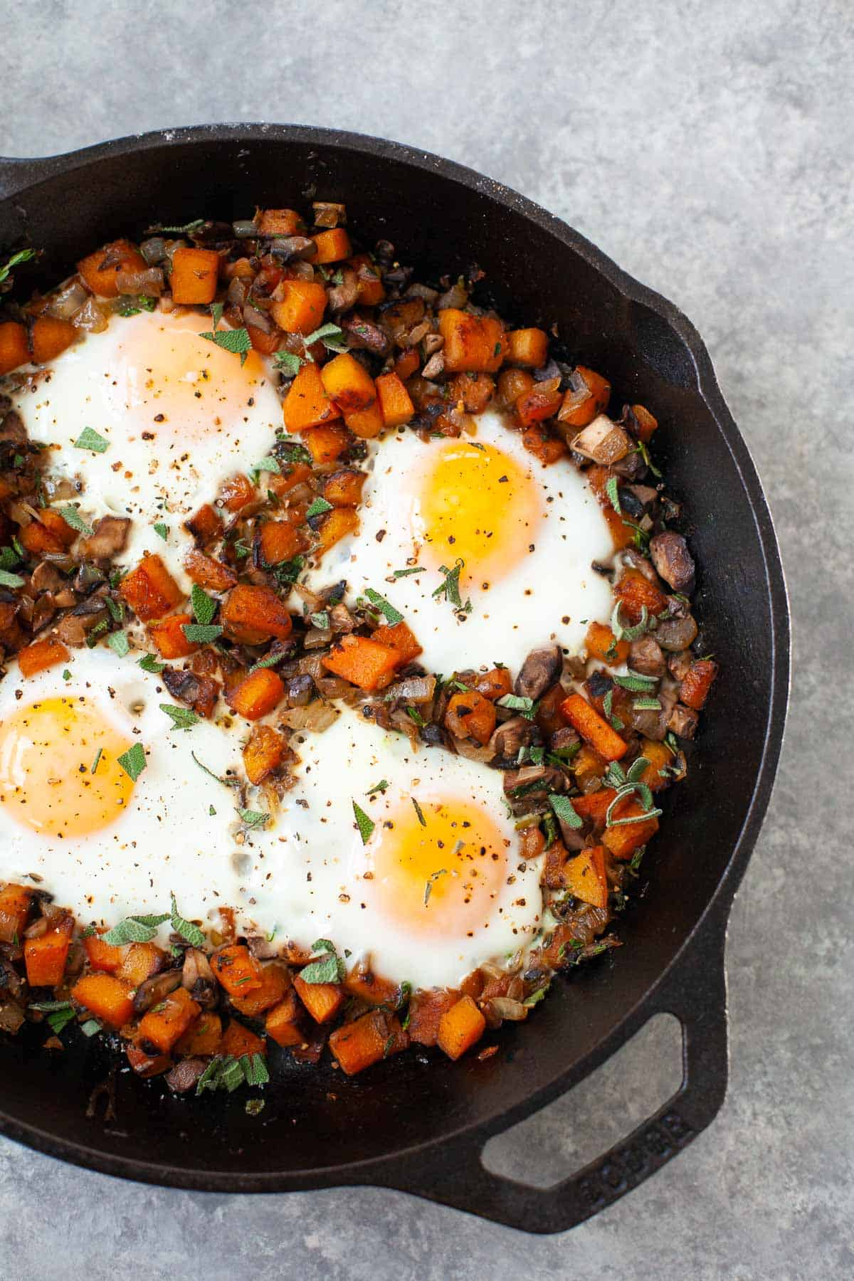 four sunny side up eggs in a skillet with butternut squash hash