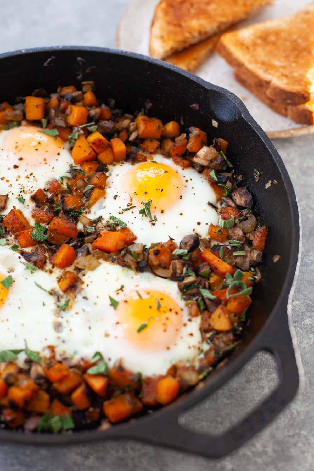 butternut squash hash with four sunny side up eggs in a skillet with plate of toast next to it
