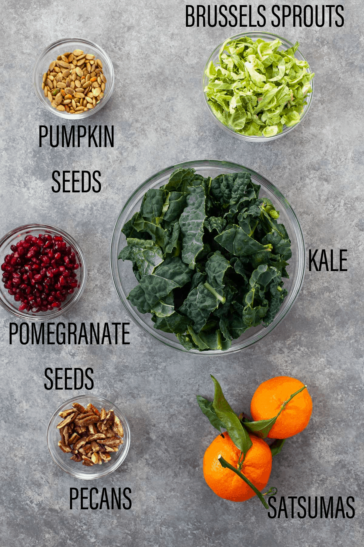 two satsumas, then separate bowls of pumpkin seeds, pecans, pomegranate seeds, brussels sprouts, and kale