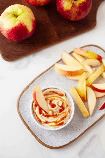 bowl of Salted Caramel Peanut Butter Apple Dip on a plate with slices apples