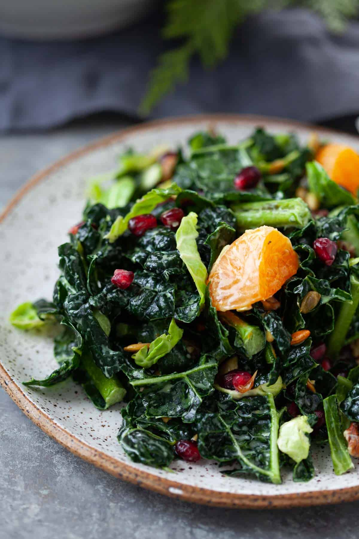 serving of kale salad with shredded brussels sprouts, pomegranate, and satsumas