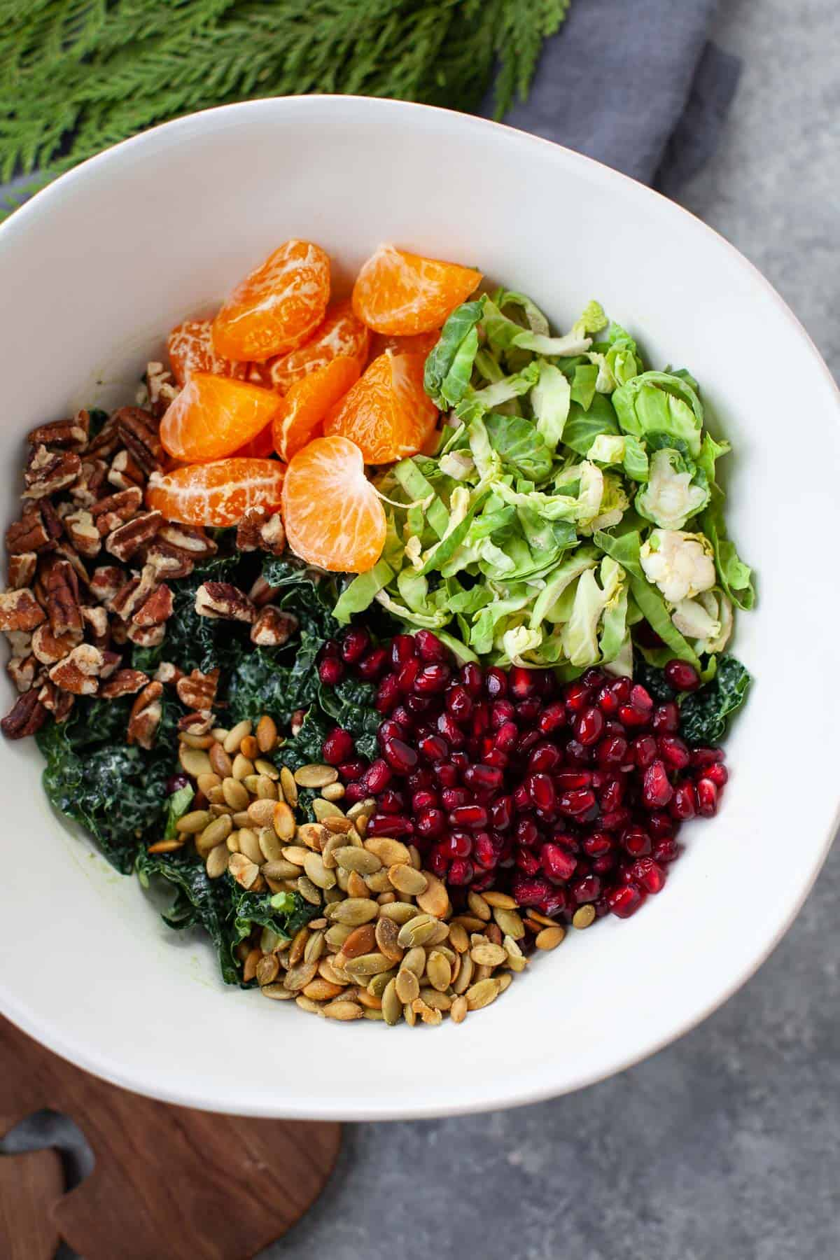 bowl filled with kale, shredded brussels sprouts, pomegranate, walnuts, and satsuma