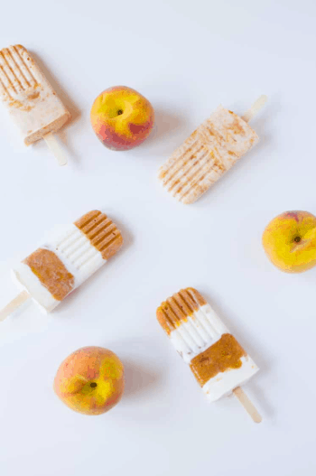 three Roasted Peaches and Cream Popsicles laid out with three peaches