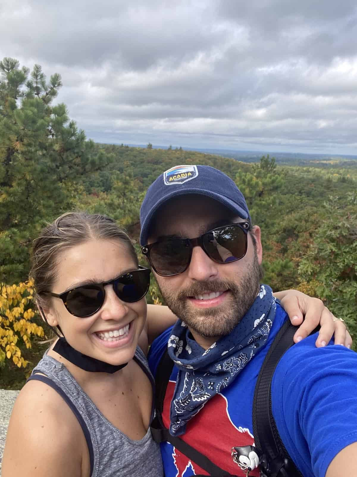 selfie image of couple hiking with sunglasses on and trees and sky in background