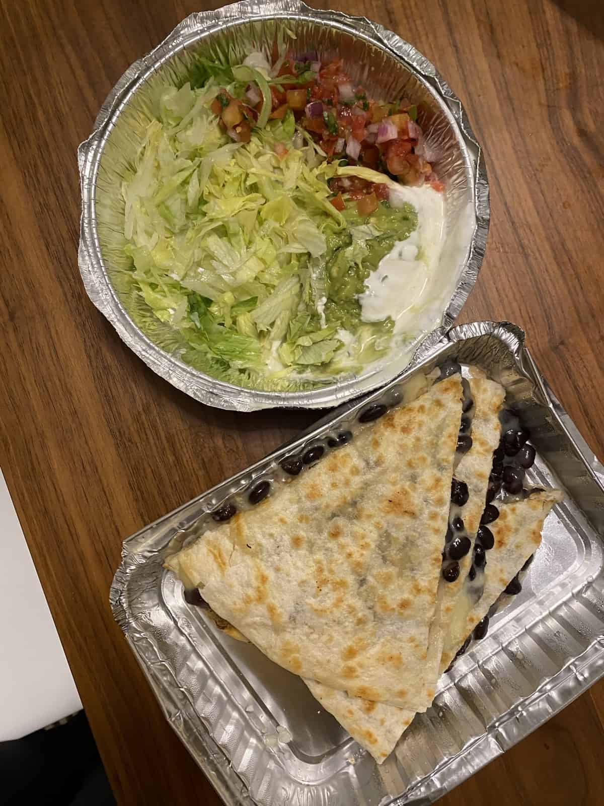 bean and cheese quesadilla in takeout container with lettuce, pico, sour cream in take out container