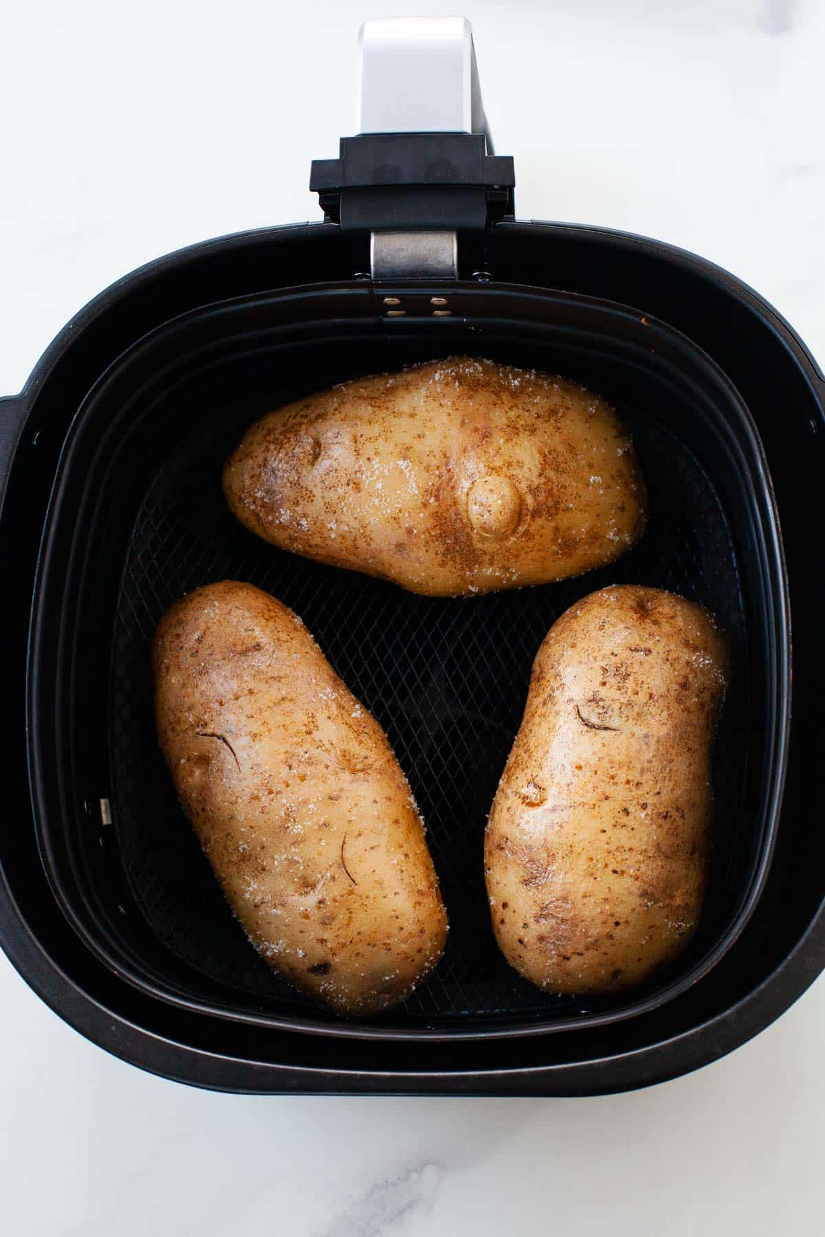 three potatoes placed inside of an air fryer