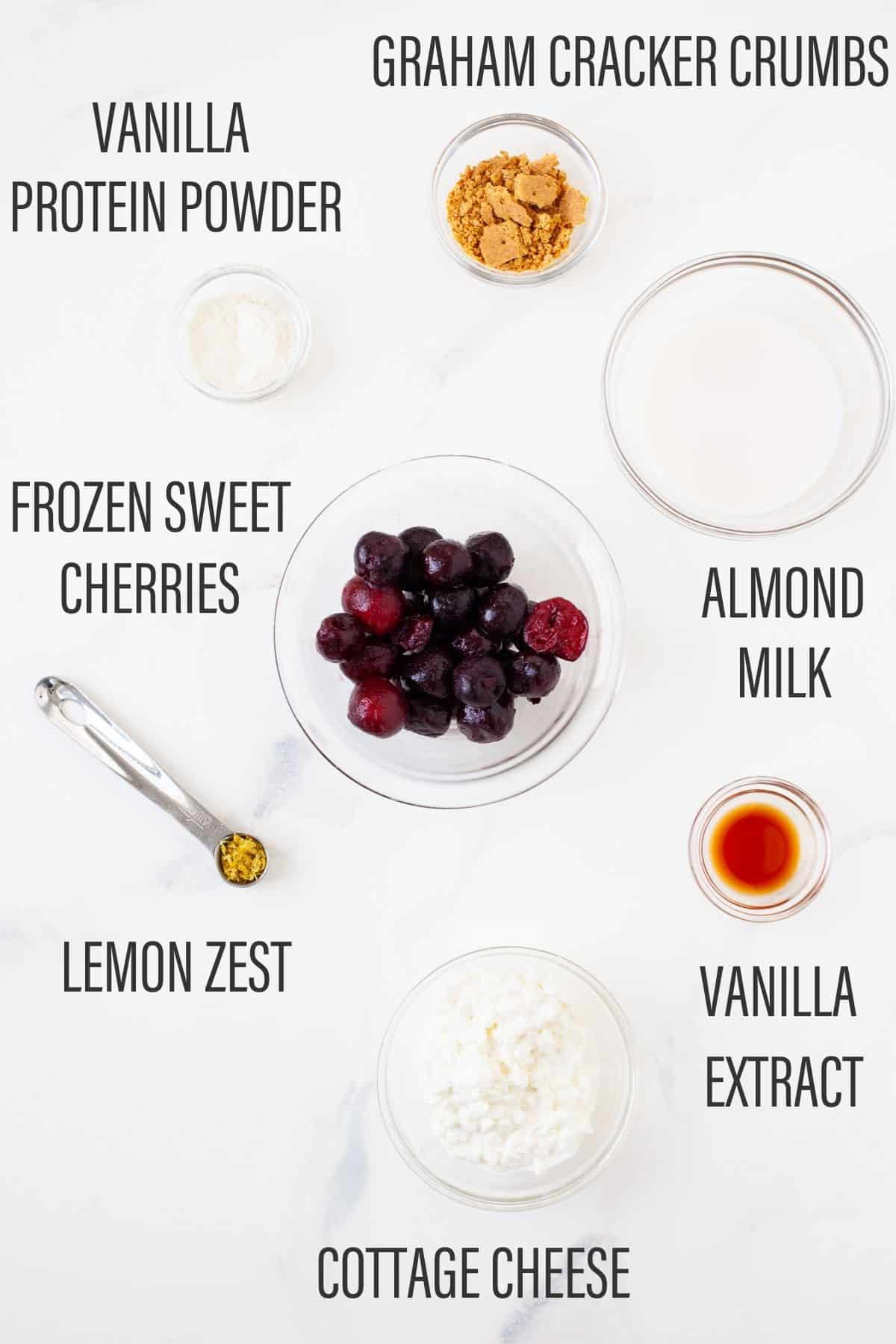 ingredients for cherry cheesecake smoothie bowl with text overlay on white surface
