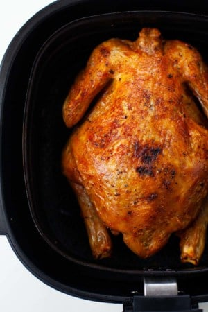 close up whole air fried chicken in black air fryer from top view