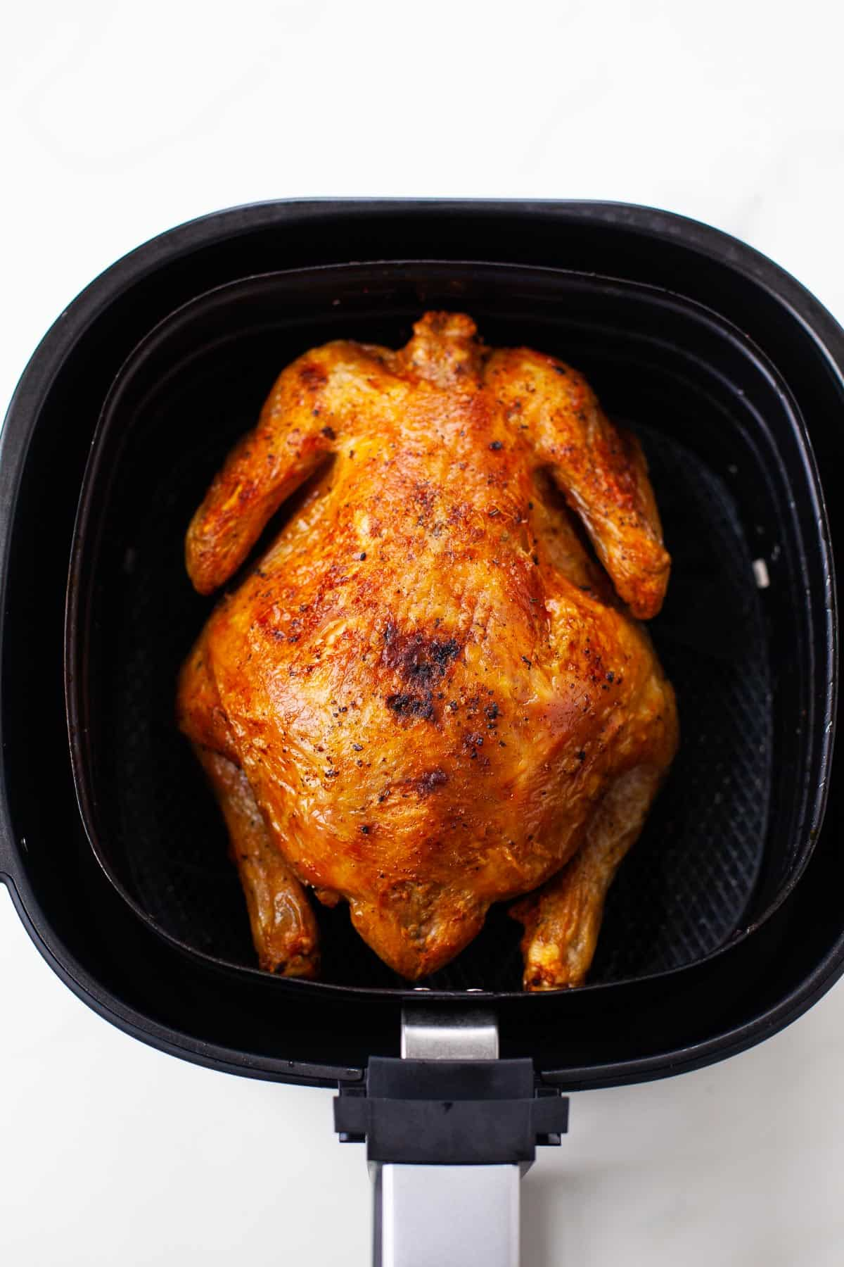 whole air fried chicken in black air fryer from top view
