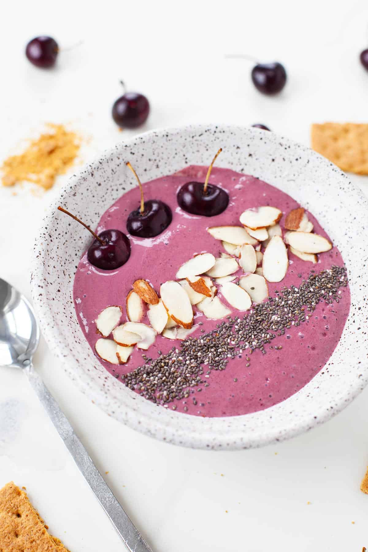 cherry cheesecake smoothie bowl with cherries, almonds, chia seeds in speckled grey bowl with graham crackers