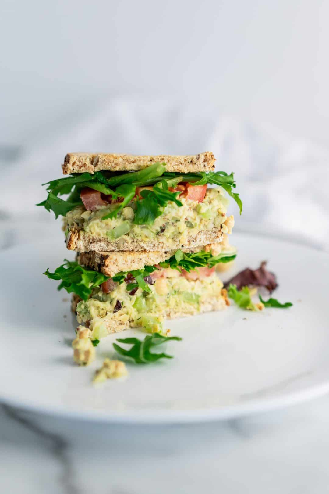 Chickpea salad, arugula, and slice of tomato between whole grain toast, sandwich halves open and stacked